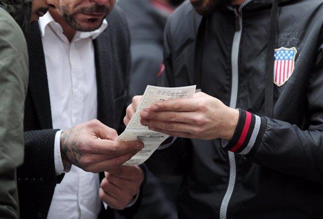 Un grup d'amics mira el nombre del bitllet de Loteria de Nadal que han comprat a la Plaza del Sol de Madrid (Espanya), a 16 de desembre del 2019 .