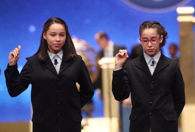 Les dues nenes de la residència de Sant Idelfons posen amb les boles corresponents al Primer Premi de la Loteria de Nadal, la grossa de la Loteria, amb el nº  26590, el qual ha sortit durant el cant de la quarta taula de la Loteria de Nadal