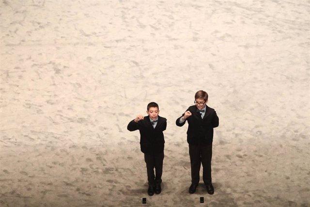Dos de los niños de la residencia de San Ildefonso, cantan uno de los quintos premios de la Lotería de Navidad, durante la celebración del Sorteo Extraordinario de la Lotería de Navidad 2019 en el Teatro Real de Madrid (España), a 22 de diciembre de 201