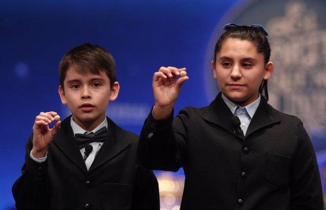 Dos dels nens de la residència de Sant Idelfons, amb les boles corresponents al Segon Premi de la Loteria de Nadal, amb el nº 10989, el qual ha sortit durant el cant de la sisena taula del Sorteig Extraordinari de la Loteria de Nadal.