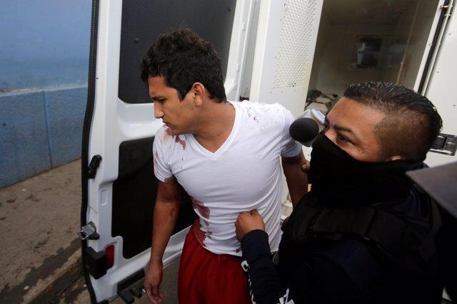 La policía escolta a un herido tras una reyerta en una cárcel de Honduras