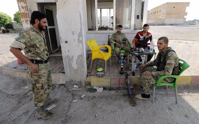 Combatientes rebeldes sirios respaldados por Turquía se sientan juntos en la ciudad fronteriza de Tal Abyad