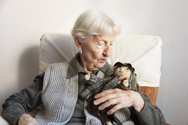 Mujer mayor con un muñeco.
