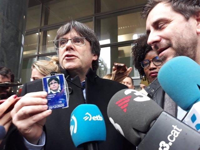 L'expresident de la Generalitat Carles Puigdemont ensenya la seva acreditació d'eurodiputat a la sortida del Parlament Europeu.