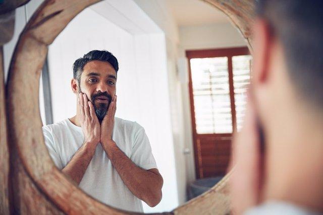 Hombre mirándose en el espejo. Crisis de los 40.