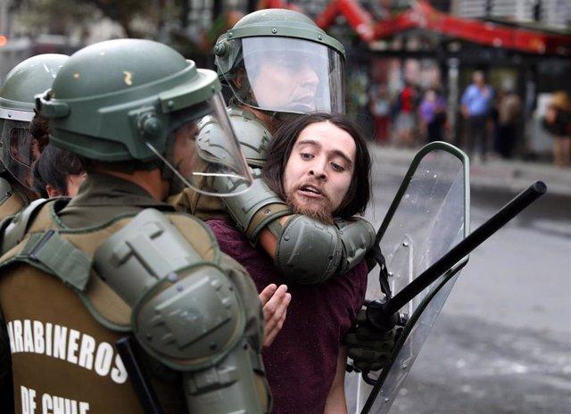 Un manifestante es reducido por agentes de los Carabineros en las protestas acontecidas en Santiago, Chile.