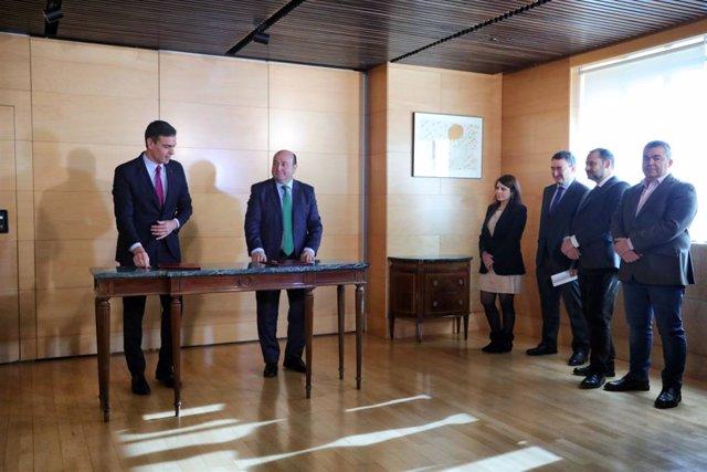 El president del Govern en funcions, Pedro Sánchez (1e) i el president de l'EBB del PNB, Andoni Ortuzar  (2e), durant la signatura de l'acord entre el PSOE i el PNB per a la investidura de Pedro Sánchez, al costat de la portaveu del PSOE al Congrés.