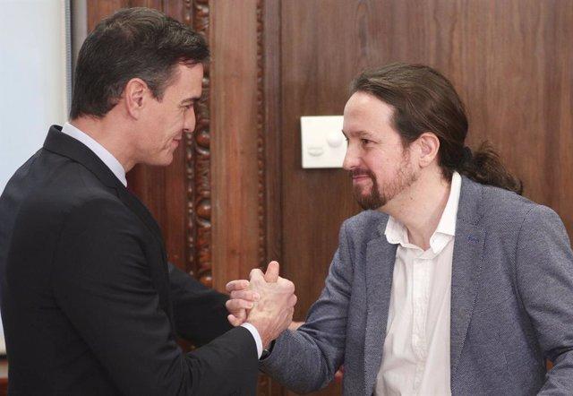 El president del Govern en funcions, Pedro Sánchez (esq) i el secretari general de Podemos, Pablo Iglesias (dr), es donen la mà durant l'acte de presentació del programa de Govern del PSOE i Unides Podem, al Congrés dels Diputats, Madrid (Espanya).