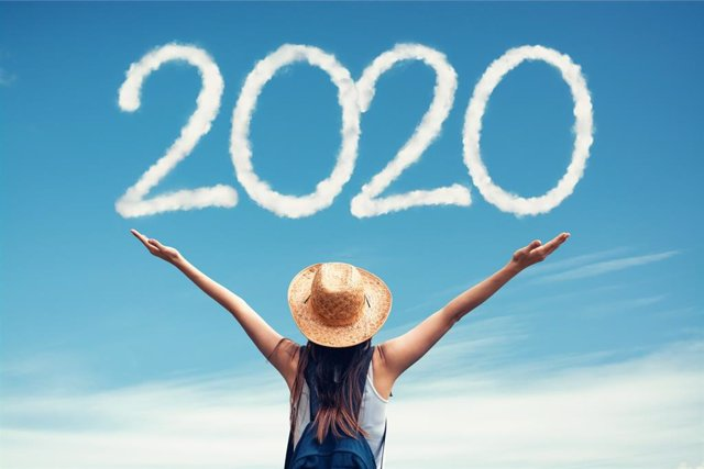 Woman with hat greets the 2020 against clouds