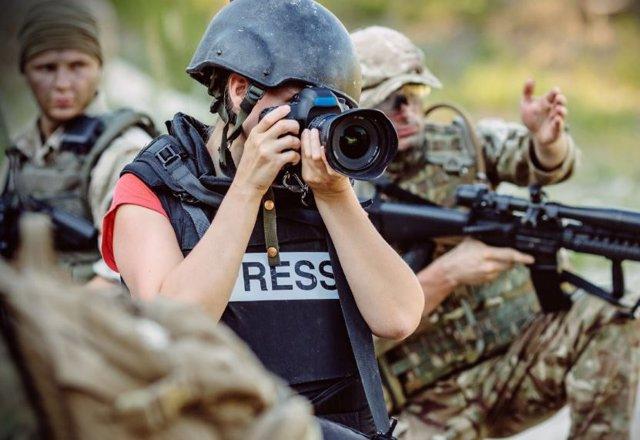 Periodista amb armilla i casc entre individus armats