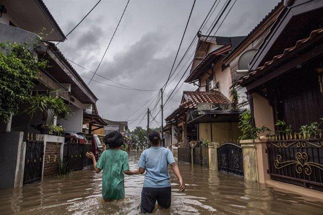 Dues dones caminen a través d'un carrer inundat després de les intenses pluges que han caigut a la capital d'Indonèsia.
