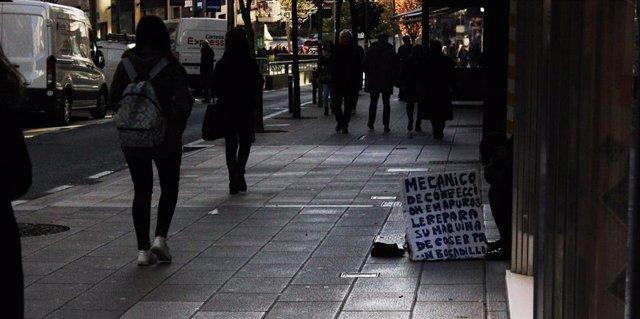 Una persona pide ayuda en la calle