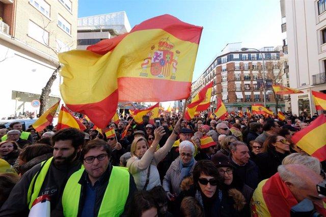 Varias personas portan banderas de España durante la manifestación convocada contra el pacto de Sánchez con Podemos y ERC, y a favor de la unidad de España