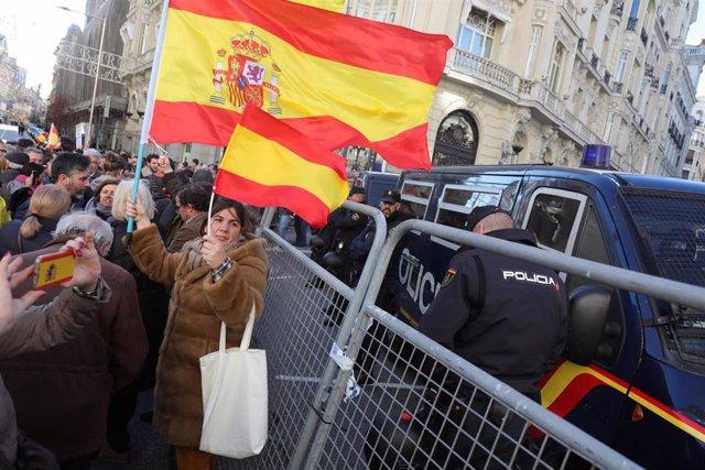 Una mujer porta dos banderas de España cerca de un furgón de policía en la calle Génova
