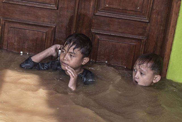 Dos nens es mantenen flotant en una de les rees inundades després de les violentes pluges en diversos punts d'Indonsia.