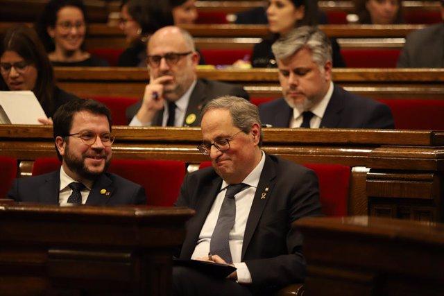 El vicepresident i el president de la Generalitat, Pere Aragonès i Quim Torra, somriuen en els seus escons durant un ple extraordinari convocat després de la decisió de la Junta Electoral Central (JEC) d'inhabilitar a Torra