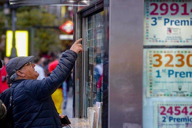 Un hombre señala el décimo de Lotería de Navidad que quiere comprar en una Administración en la plaza de Puerta del Sol, en Madrid (España), a 18 de noviembre de 2019.