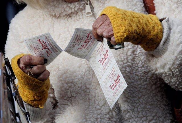 Una lotera entrega una tira de boletos de la Lotería del Niño. (Archivo).