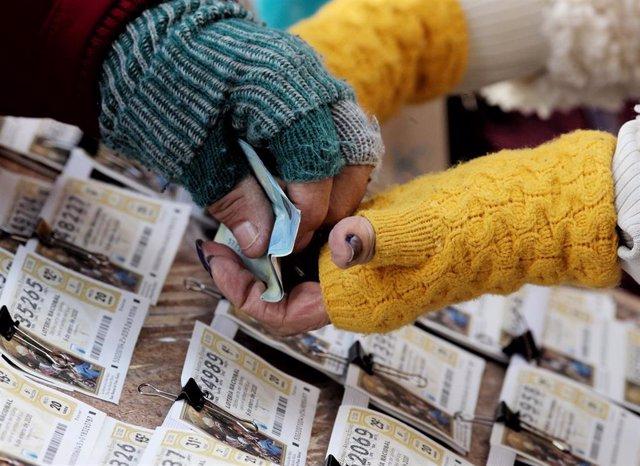 Una mujer comprando un boleto de la Lotería del Niño. (Archivo).