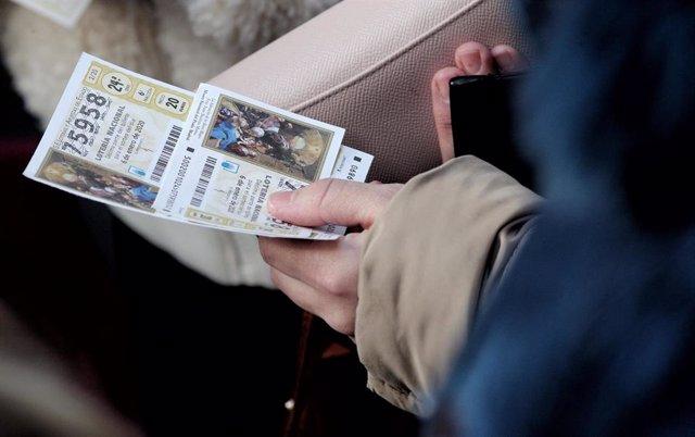 Una mujer compra varios boletos de la Lotería del Niño.