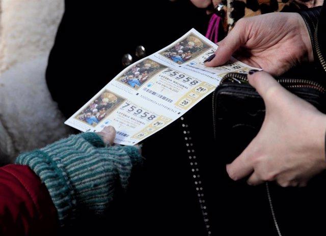 Una mujer compra varios boletos de la Lotería del Niño. (Archivo).