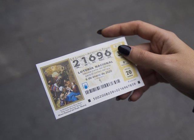 Una dona mostra el seu bitllet del sorteig de Reis.