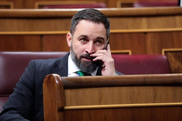 El presidente de VOX, Santiago Abascal, habla por teléfono desde su escaño momentos antes de comenzar la segunda sesión del debate de investidura del candidato socialista a la Presidencia de Gobierno en la XIV Legislatura en Madrid (España).