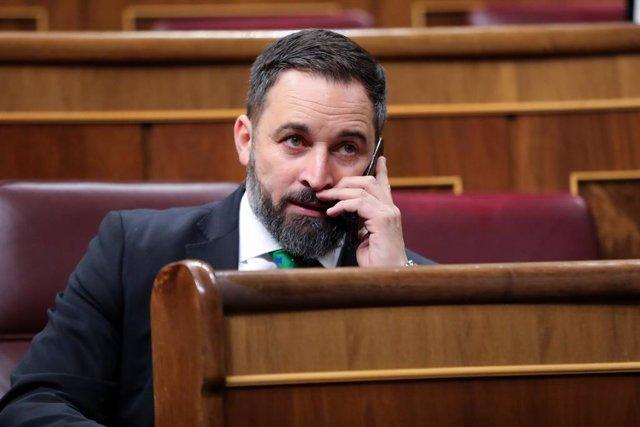 El president de Vox, Santiago Abascal, parla per telèfon des del seu escó moments abans de començar la segona sessió del debat d'investidura del candidat socialista a la Presidència de Govern en la XIV Legislatura a Madrid (Espanya).