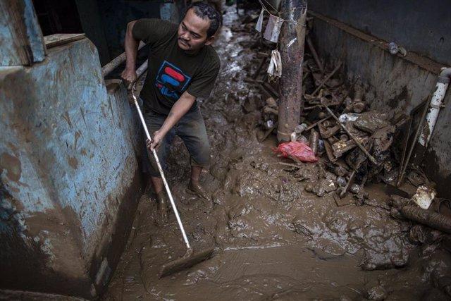 Un hombre intenta limpiar su casa del lodo provocado por las fuertes lluvias caídas en Yakarta, Indoensia, desde Año Nuevo (2020).