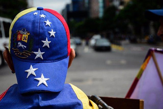 Un hombre con una gorra con la bandera venezolana
