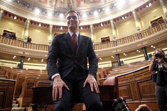 El presidente del Gobierno, Pedro Sánchez, posa sonriente en el hemiciclo del Congreso de los Diputados, tras obtener una votación favorable a su investidura (de 167 a 165 y 18 abstenciones) y convertirse en el presidente electo de la XIV Legislatura