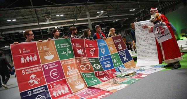 El personaje 'SustainaClaus' junto a un cartel de los Objetivos de Desarrollo Sostenible (ODS) de la Agenda 2030.