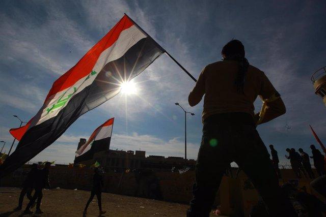 Un manifestante con una bandera de Irak