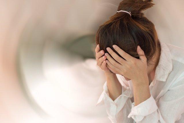 Concepto de enfermedad de vértigo y de ansiedad. Mujer con las manos sobre la cabeza, dolor de cabeza, mareos, sensación de mareo, un problema con el oído interno, el cerebro o la vía del nervio sensorial.