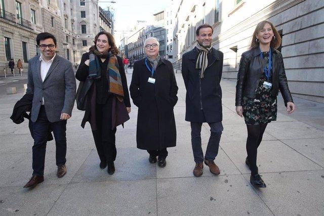 Manuel Castells, en el centro de la imagen, junto a la alcaldesa de Barcelona, Ada Colau, y otros representantes de los 'comunes', este 7 de enero frente al Congreso.