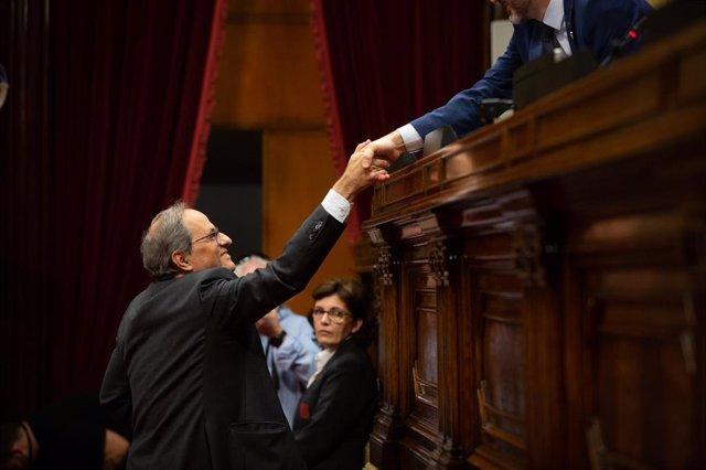 El president de la Generalitat de Catalunya, Quim Torra, saluda el president de Parlament, Roger Torrent, durant la seva intervenció en una sessió plenària del Parlament (Arxiu).