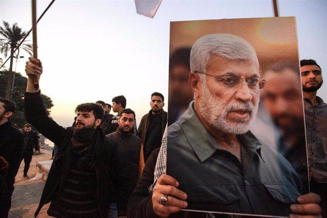 Seguidores de la coalición de milicias Fuerzas de Movilización Popular (FMP) con una imagen de su 'número dos', Abú Mahdis al Muhandis, muerto en un bombardeo de EEUU