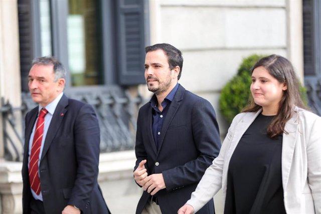 El secretario general del PCE y diputado de Unidas Podemos, Enrique Santiago (i) y el coordinador federal de Izquierda Unida (IU) y diputado de Unidas Podemos, Alberto Garzón, llegan al Congreso de los Diputados para la segunda votación para la investidur