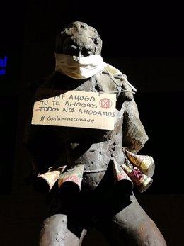 Una de las esculturas con los carteles-protesta