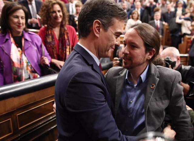 El secretario general de Podemos, Pablo Iglesias, felicita al al presidente del Gobierno, Pedro Sánchez, tras ser elegido al finalizar la segunda sesión de votación para la investidura del candidato socialista a la Presidencia del Gobierno