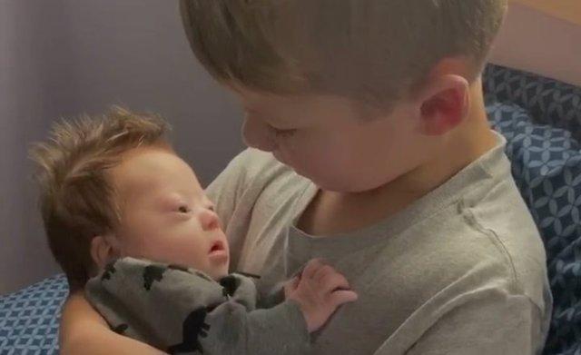 Un niño de seis años le canta a su hermano recién nacido con Síndrome de Down