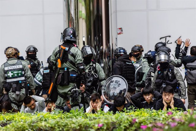 """05 January 2020, China, Hong Kong: Riot police arrest protesters during a protest against """"parallel traders"""", who buy the goods in the Special Administrative Region in order to resell them on the Chinese mainland."""