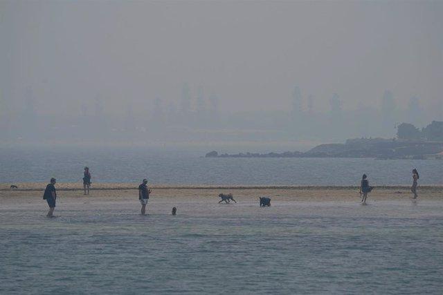 Personas son fotografiadas en una playa mientras una tupida neblina procedente de los fuertes incendios forestales que están arrasando Australia se asienta sobre el cielo de Melbourne.