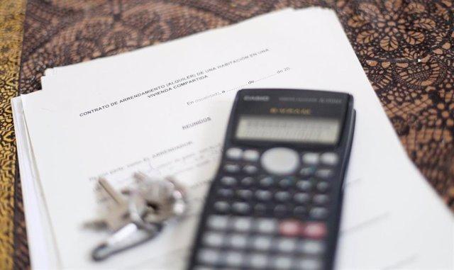 Una calculadora y unas llaves sobre un contrato de arrendamiento (alquiler) de una habitación en una vivienda compartida.