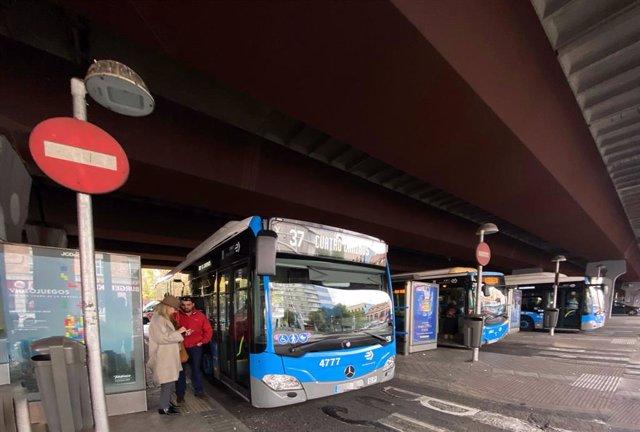 Varios autobuses de la EMT paran para recoger y dejar viajeros durante su ruta por Madrid.