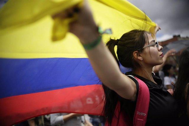 Una manifestante con la bandera de Colombia