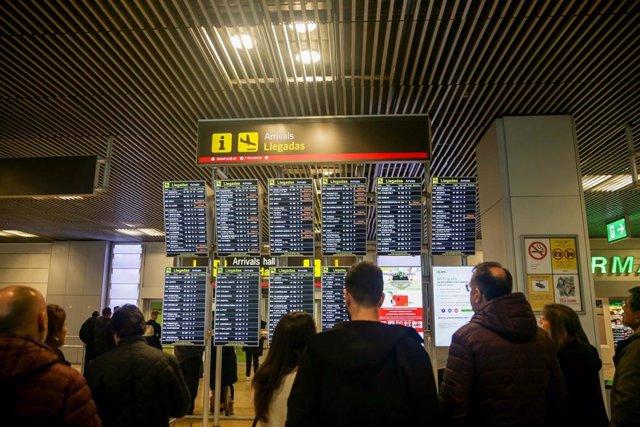 Varias personas comprueban la llegada de vuelos en varios paneles luminosos en el inicio de la operación salida de Navidad en el aeropuerto Adolfo Suárez Madrid-Barajas, en Madrid a 20 de diciembre de 2019.