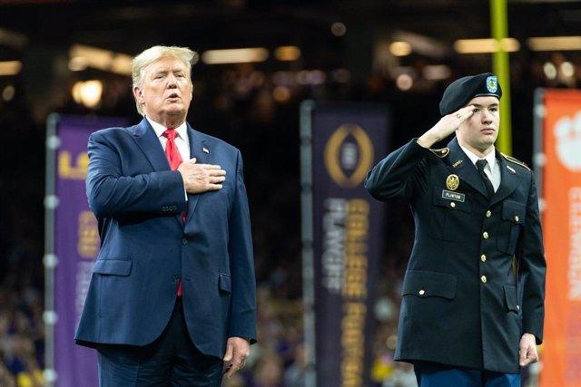 El presidente de Estados Unidos, Donald Trump, canta el himno durante un partido de fútbol americano de la Liga Universitaria en Nueva Orleans.