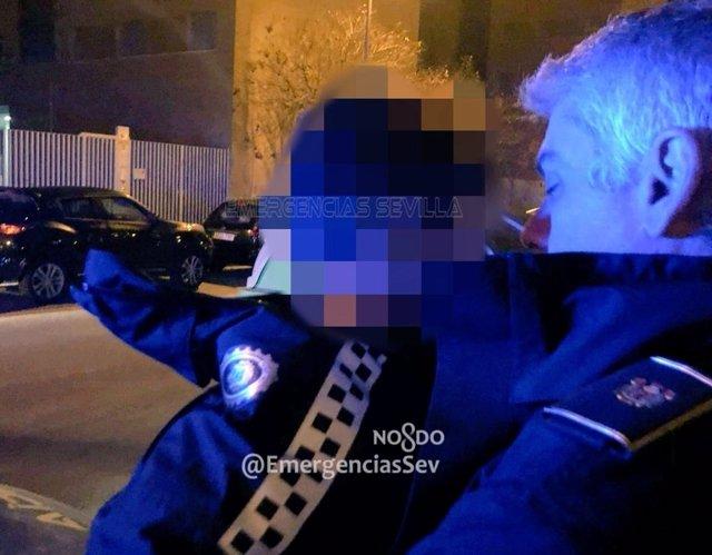Un agente arropa a un niño de cuatro años perdido en una calle de Sevilla.