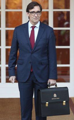 El ministro de Sanidad, Salvador Illa, posa con la cartera de su ministerio, a su llegada a La Moncloa